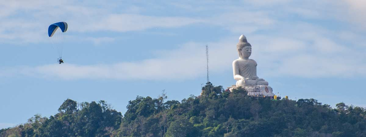 big buddha atop the nakkerd hills seen from the sea with a microlite passing by can be seen from our chalong apartments