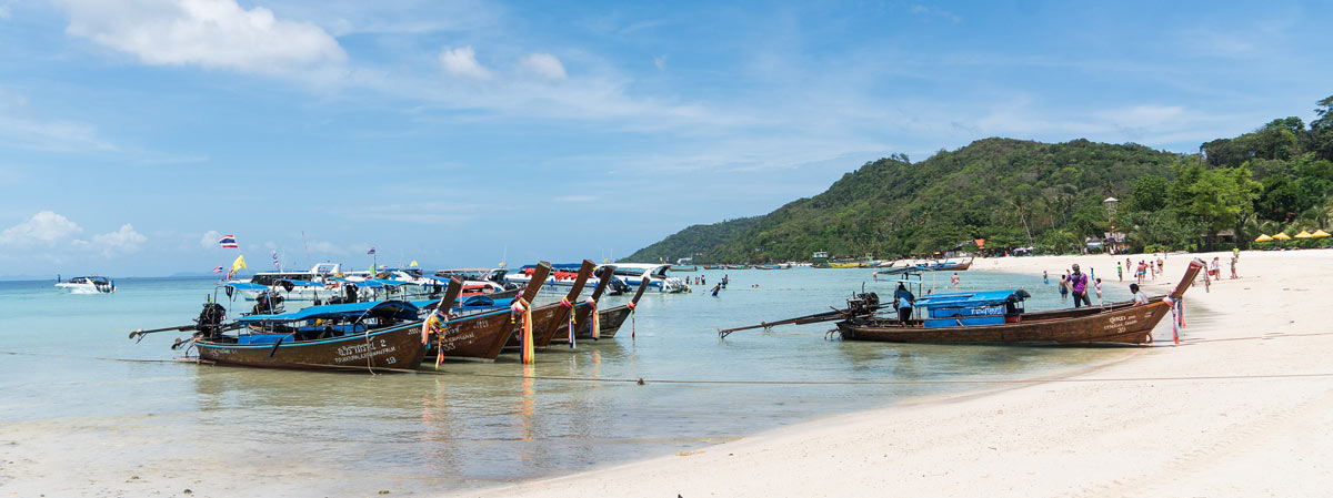 longtail boats at phi phi island with the beach an jungle accessible for chalong bay for day trips