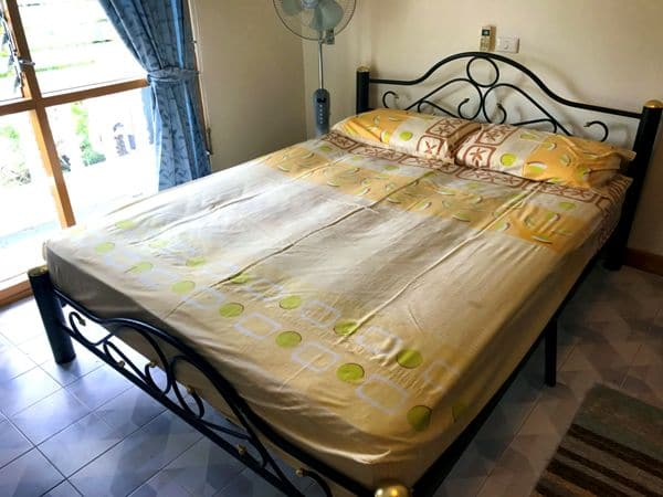 iron framed queen sized bed with fan and fitted sheets in one of our standard Rawai apartment