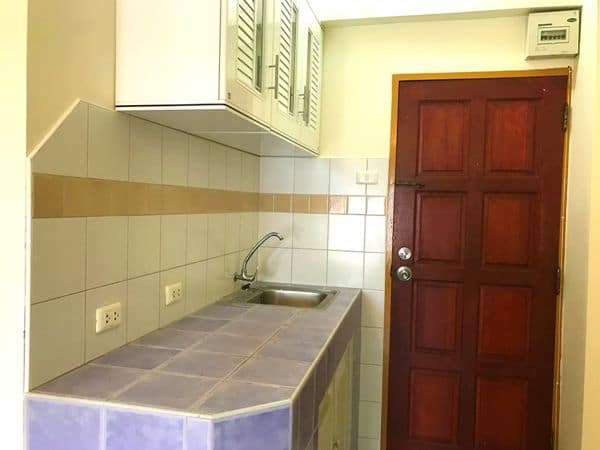 tiled kitchen with sink and electric sockets and storage cupboards at the entrance of one of our standard Rawai apartments